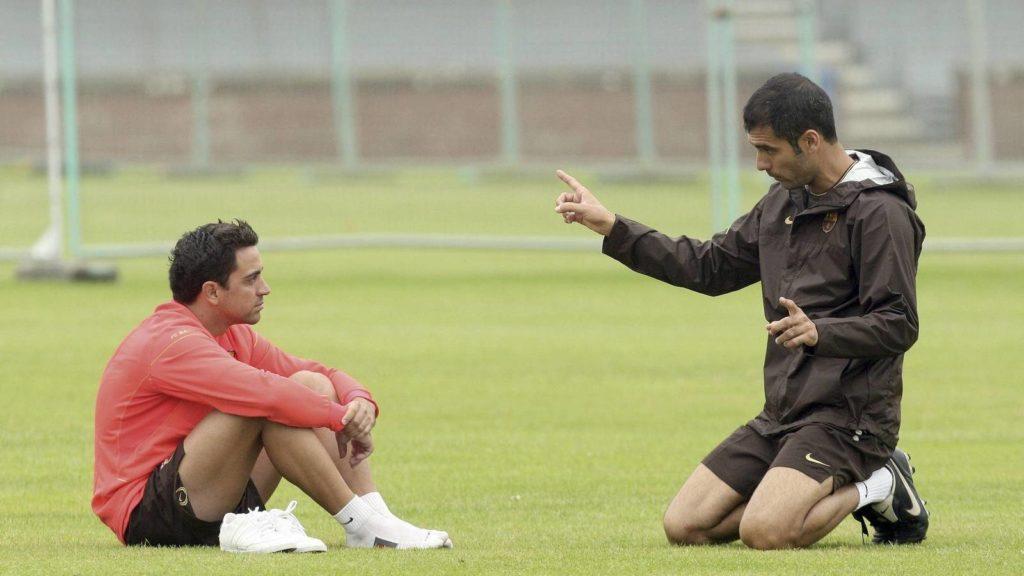 Guardiola explicándole a Xavi aspectos del juego.